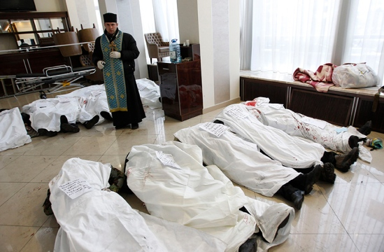 A priest stands in the lobby of the hotel Ukraine near bodies of anti-government protesters killed during clashes with riot police in Kiev